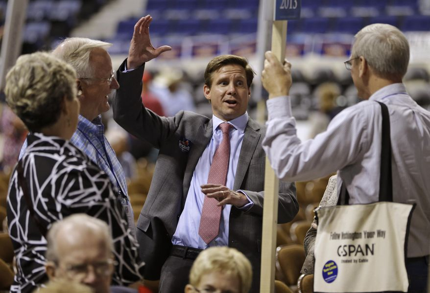 """FILE - In this May 17, 2013, file photo, candidate for Governor of Virginia, Pete Snyder, center, gestures as he talks to delegates during the opening of the Virginia Republican convention in Richmond, Va.  The top GOP contenders for governor in Virginia say """"election integrity"""" is a high priority. The candidates say change is needed to restore credibility to the voting process, whether that involves tightening voter ID laws, making the Department of Elections politically independent, or cleaning up voter rolls. (AP Photo/Steve Helber, File)"""