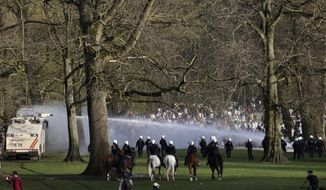 Police use a water cannon during protests at a park in Brussels, Thursday, April 1, 2021. Belgian police have clashed with a large crowd in one of Brussels largest parks, as thousands of revelers had gathered for an unauthorized event despite coronavirus restrictions. (AP Photo/Olivier Matthys)
