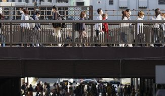 People wear face masks as they make their way in Osaka, western Japan Wednesday, March 31, 2021. Japan is set to designate Osaka and two other prefectures for new virus control steps Thursday as infections in those areas rise less than four months before the Tokyo Olympics. (Kyodo News via AP)