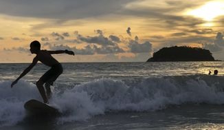 A surfer catches a wave as the sun sets over Kata Beach on the resort island of Phuket, Thailand on Sunday, May 26, 2019. Thailand plans to allow vaccinated foreigners to visit the southern resort island of Phuket without quarantining on arrival in a step toward reviving the country's big but battered tourism industry. (AP Photo/Adam Schreck)