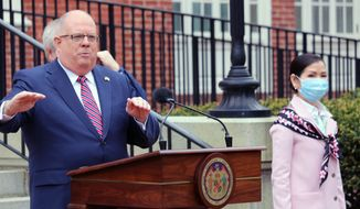 In this Monday, April 20, 2020, file photo, Maryland Gov. Larry Hogan speaks at a news conference in Annapolis, Md., with his wife, Yumi Hogan, right, where the governor announced Maryland has received a shipment from a South Korean company to boost the state's ability to conduct tests for COVID-19 by 500,000. Maryland auditors have found Gov. Larry Hogan's administration failed to follow state procurement regulations when it bought 500,000 COVID-19 tests from a South Korean company last year. (AP Photo/Brian Witte, File)