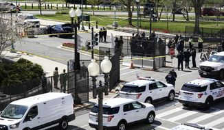Police officers gather near a car that crashed into a barrier on Capitol Hill in Washington, Friday, April 2, 2021. (AP Photo/J. Scott Applewhite)