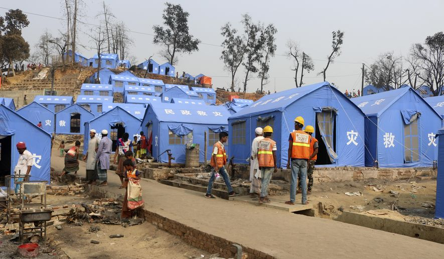 Volunteers from aid agencies rebuild shelters for Rohingya refugees who lost their dwellings to a devastating fire at Balukhali camp at Ukhiya in Cox's Bazar district, Bangladesh, Wednesday, March 24, 2021. At least 15 people, including children were killed and thousands of Rohingya refugees became homeless in Monday's fire. (AP Photo/ Shafiqur Rahman)