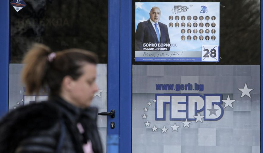 A woman passes by a poster depicting Bulgarian prime minister Boyko Borissov, in Sofia, Bulgaria, Wednesday, March 31, 2021. After months of nationwide anti-government protests over corruption, stalled reforms and a stagnating economy in the EU's poorest member state, Bulgarians are gearing up for a parliamentary election overshadowed by a deadly pandemic. (AP Photo/Valentina Petrova)