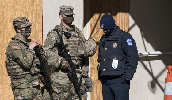 In this file photo, a U.S. Capitol Police officer, right, stands with two National Guard members near the scene where a fellow officer was killed after a man rammed a car into two officers at a barricade outside the U.S. Capitol and then emerged wielding a knife, on Capitol Hill in Washington, Friday, April 2, 2021. (AP Photo/J. Scott Applewhite)  **FILE**