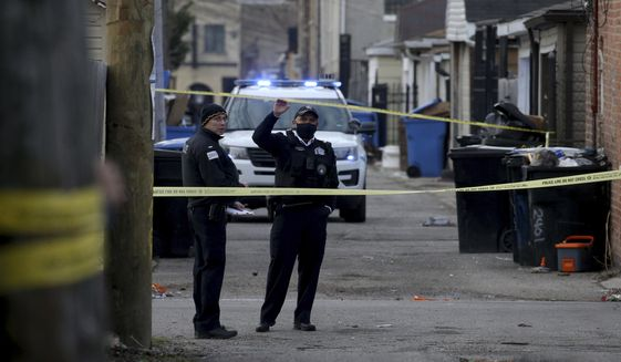 Police work at the scene of a fatal shooting of a 13-year-old boy by a Chicago Police officer on Monday, March 29, 2021 in Chicago.  Calls for the release of body camera video of the fatal shooting of the 13-year-old boy by a Chicago Police officer are growing louder both within and outside the department. As the agency that investigates police shootings says it is investigating if there is a legal way to release the video of Monday's shooting of Adam Toledo, Police Superintendent David Brown and Mayor Lori Lightfoot both say it should be released.  (Antonio Perez/Chicago Tribune via AP)