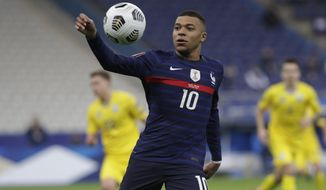 France's Kylian Mbappe controls the ball during the World Cup 2022 group D qualifying soccer match between France and Ukraine at the Start de de France stadium, in Saint Denis, north of Paris, Wednesday, March 24, 2021. (AP Photo/Thibault Camus)