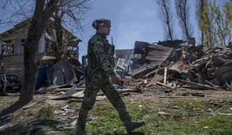 An Indian paramilitary soldier walks past a house destroyed during a gunbattle in Pulwama, south of Srinagar, Indian controlled Kashmir, Friday, April 2, 2021. Anti-India protests and clashes have erupted between government forces and locals who thronged a village in disputed Kashmir following a gunbattle that killed three suspected militants. Police say the gunfight on Friday erupted shortly after scores of counterinsurgency police and soldiers launched an operation based on tip about presence of militants in a village in southern Pulwama district. (AP Photo/ Dar Yasin)