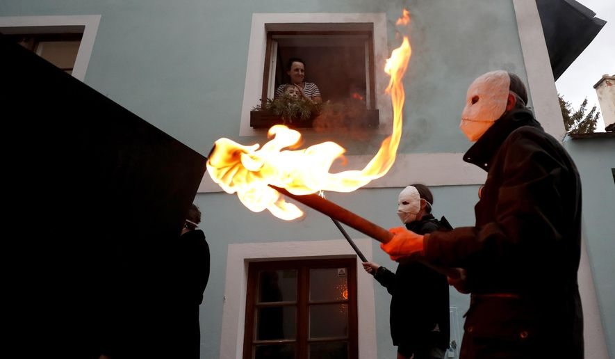 People watch from the window of their home as participants dressed in black, wearing masks, beating drums and pushing small carts making a synchronized and loud sound take part in an Easter procession marching through the streets of Ceske Budejovice, Czech Republic, Thursday, April 1, 2021. (AP Photo/Petr David Josek)