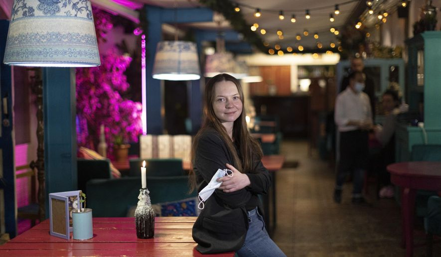 """Valentina Konstantinova, co-founder of the Skazka, or """"Fairytale,"""" a boutique hotel in eastern Moscow, stands during her interview with The Associated Press on Tuesday, March 23, 2021. When Russia locked down for the coronavirus a year ago, her 18-room emptied out within a couple of days. A year later, Skazka is still open — thanks to some creative thinking by Konstantinova, who makes up some revenue by having added a restaurant that serves Indian cuisine. (AP Photo/Alexander Zemlianichenko)"""