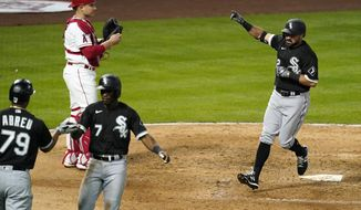 Chicago White Sox's Adam Eaton, right, scores after hitting a two-run home run as shortstop Tim Anderson, second from right, is congratulated by Jose Abreu, left, and Los Angeles Angels catcher Max Stassi watches during the fifth inning of an Opening Day baseball game Thursday, April 1, 2021, in Anaheim, Calif. (AP Photo/Mark J. Terrill)