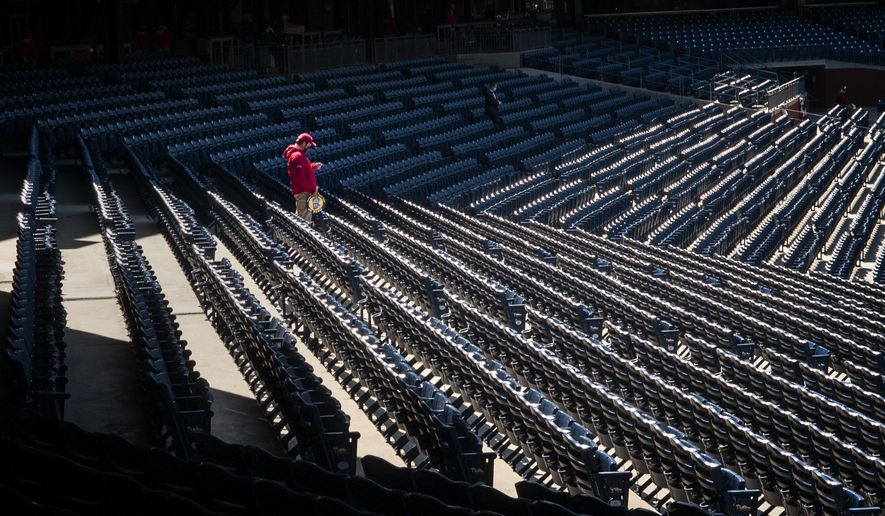 A Philadelphia Phillies usher walks through the empty stands before the start of a baseball game against the Atlanta Braves, Saturday, April 3, 2021, in Philadelphia. (AP Photo/Laurence Kesterson)