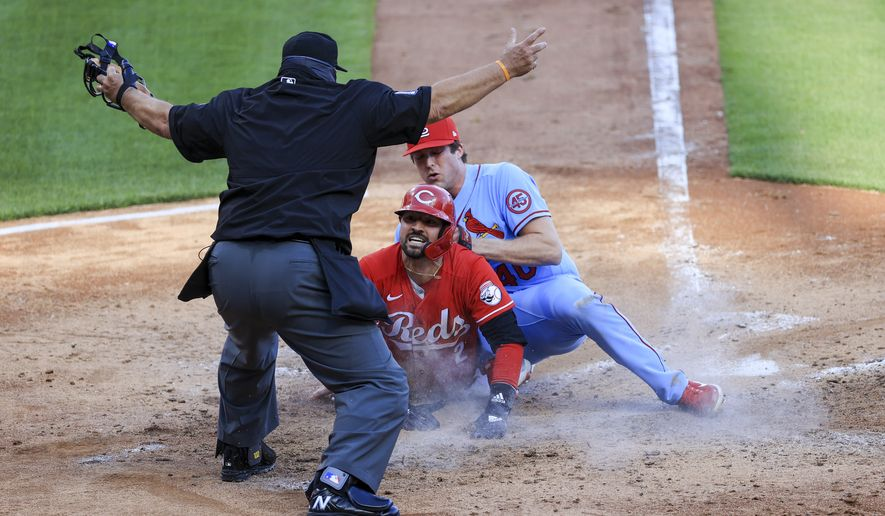 MLB umpire Tony Randazzo, left, signals as Cincinnati Reds' Nick Castellanos, middle, scores a run as he slides past the tag of St. Louis Cardinals' Jake Woodford during a baseball game in Cincinnati, Saturday, April 3, 2021. The Reds won 9-6. (AP Photo/Aaron Doster)