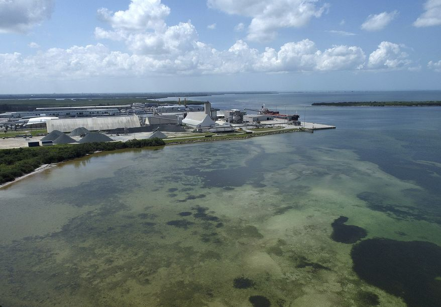 This photo taken by a drone shows the old Piney Point phosphate mine, Saturday, April 3, 2021 in Bradenton, Fla. Florida Gov. Ron DeSantis declared a state of emergency Saturday after a significant leak at a large pond of wastewater threatened to flood roads and burst a system that stores polluted waters. The pond where the leak was discovered is at the old Piney Point phosphate mine, sitting in a stack of phosphogypsum, a waste product from manufacturing fertilizer that is radioactive. (Tiffany Tompkins/The Bradenton Herald via AP)