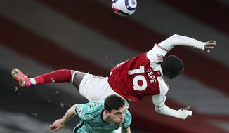 Arsenal's Nicolas Pepe, right, falls over Liverpool's Andrew Robertson during the English Premier League soccer match between Arsenal and Liverpool at the Emirates Stadium in London, England, Saturday, April 3, 2021. (Catherine Ivill/Pool via AP)