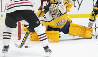 Nashville Predators goaltender Juuse Saros reaches for the puck in the first period of an NHL hockey game against the Chicago Blackhawks Saturday, April 3, 2021, in Nashville, Tenn. (AP Photo/Mark Humphrey)