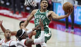 Milwaukee Bucks forward Giannis Antetokounmpo, right, shoots over Portland Trail Blazers forward Robert Covington during the second half of an NBA basketball game in Portland, Ore., Friday, April 2, 2021. (AP Photo/Craig Mitchelldyer)