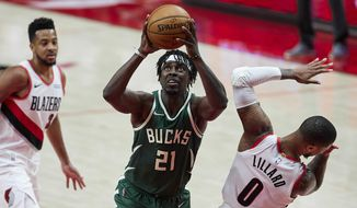 Milwaukee Bucks guard Jrue Holiday, center, drives to the basket past Portland Trail Blazers guard Damian Lillard, right, during the second half of an NBA basketball game in Portland, Ore., Friday, April 2, 2021. (AP Photo/Craig Mitchelldyer)