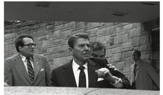 FILE - In this Monday, March 30, 1981 combination file photos, President Reagan waves, then looks up before being shoved into Presidential limousine by Secret Service agents after being shot outside a Washington hotel. f you're about 50 or older, you probably remember where you were when you learned President Ronald Reagan was shot in an assassination attempt 40 years ago on March 30, 1981. Savannah cardiologist Dr. Randy Bottner definitely does. (AP Photo/Ron Edmonds, File)