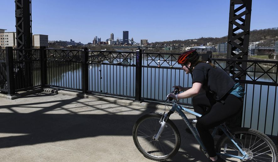 The Pittsburgh skyline can be seen from the Hot Metal Bridge as a bicyclist moves along the Great Allegheny Passage in the South Side on Monday, March 22, 2021. It has been an adventure, of the good kind, for many of the small towns along the 150-mile former railroad which runs through Allegheny, Westmoreland, Fayette and Somerset counties. The economic impact it has bestowed has been huge, said Bryan Perry, director of the Great Allegheny Passage Conservancy, a nonprofit that supports and coordinates work among all the trail volunteer groups. (Kristina Serafini/Pittsburgh Tribune-Review via AP)
