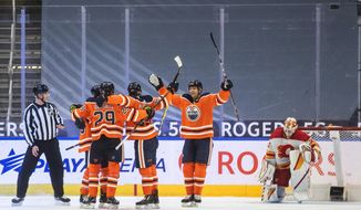 Edmonton Oilers players celebrate a goal on Calgary Flames goalie Jacob Markstrom, right, during the third period of an NHL hockey game Friday, April 2, 2021, in Edmonton, Alberta. (Jason Franson/The Canadian Press via AP)