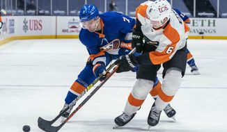 New York Islanders right wing Jordan Eberle, left, and Philadelphia Flyers defenseman Travis Sanheim vie for the puck during the second period of an NHL hockey game Saturday, April 3, 2021, at Nassau Coliseum in Uniondale, N.Y. (AP Photo/Corey Sipkin).