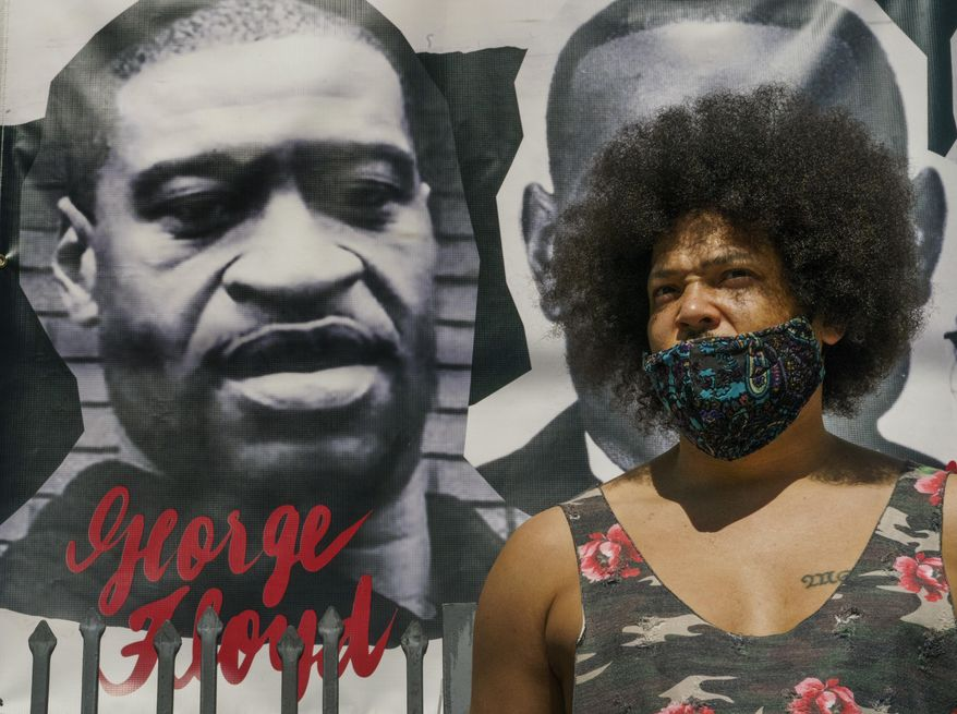 Actor Steven Thompson poses for a picture next to a poster of George Floyd in Los Angeles Friday, April 2, 2021. Thompson is choosing not to watch the televised trial of Derek Chauvin, the white police officer charged in the death of George Floyd, has provoked strong emotions among many Black men and women, all tinged with an underlying dread that it could yield yet another devastating disappointment, even though he feels there is a strong case against him. (AP Photo/Damian Dovarganes)