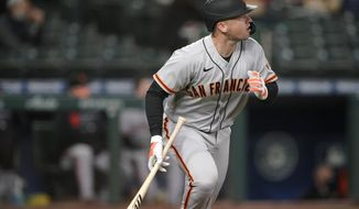 San Francisco Giants' Buster Posey watches his solo home run during the third inning of the team's baseball game against the Seattle Mariners, Friday, April 2, 2021, in Seattle. (AP Photo/Ted S. Warren)