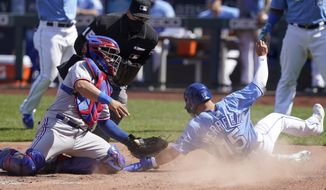 Kansas City Royals Whit Merrifield (15) beats the tag by Texas Rangers catcher Jose Trevino, left, during the sixth inning of a baseball game at Kauffman Stadium in Kansas City, Mo., Saturday, April 3, 2021. (AP Photo/Orlin Wagner)