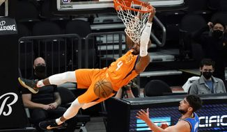 Phoenix Suns guard Jevon Carter (4) dunks over Oklahoma City Thunder guard Ty Jerome during the first half of an NBA basketball game Friday, April 2, 2021, in Phoenix. (AP Photo/Rick Scuteri)