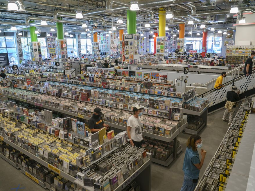 Customers shop at the newly reopened Amoeba Music, the World's largest independent record store, in Los Angeles Friday, April 2, 2021. Most of California's 58 counties are in the red tier, but big population centers like San Francisco, Santa Clara County and Los Angeles County are in the less restrictive orange tier. Just two counties are in the lowest yellow tier. California on Friday cleared the way for people to attend indoor concerts, theater performances and NBA games for the first time in more than a year as the rate of people testing positive for the coronavirus in the state nears a record low. (AP Photo/Damian Dovarganes)