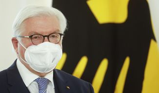 German President Frank Walter Steinmeier attends a ceremony to honor people for their services during the coronavirus pandemic with state's cross of merit at Bellevue Palace in Berlin, Germany, Friday, March 26, 2021. (AP Photo/Markus Schreiber, Pool)