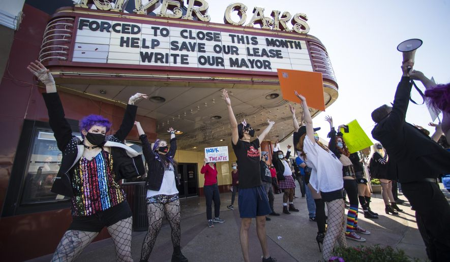"""Fans and patrons of the Landmark River Oaks Theatre do the """"Time Warp"""", from the """"Rocky Horror Picture Show"""" as they demonstrate against the potential closure of the historic movie theater Sunday, March 7, 2021, in Houston. The historic Houston theater that director Richard Linklater called his """"film school"""" and that for decades was the place to catch hard-to-find independent and foreign films has closed for good. Like many U.S. movie theaters and other businesses, the River Oaks Theatre was a victim of the coronavirus pandemic.. ( Brett Coomer/Houston Chronicle via AP)"""
