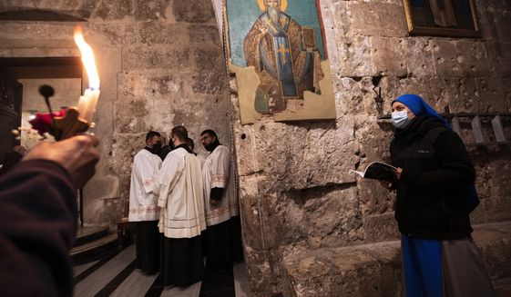 Priests and a nun wearing face masks attend Easter Sunday Mass at the Church of the Holy Sepulchre, where many Christians believe Jesus was crucified, buried and rose from the dead, in the Old City of Jerusalem, Sunday, April 4, 2021. (AP Photo/Oded Balilty)