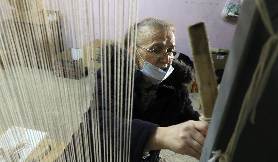 Hate Ora, 64, or 'Aunt Hate' as everyone knows her, weaving a carpet in Kukes town, northeastern Albania, Friday, March 12, 2021. Albania once had 13 former state-run factories that produced carpets, rugs, fez hats, felt folk costumes and other handicrafts. Kukes, a town northeast of the capital, Tirana, alone employed more than 1,200 women as weavers. When the country's communist era ended in 1990, the local factory closed. (AP Photo/Hektor Pustina)