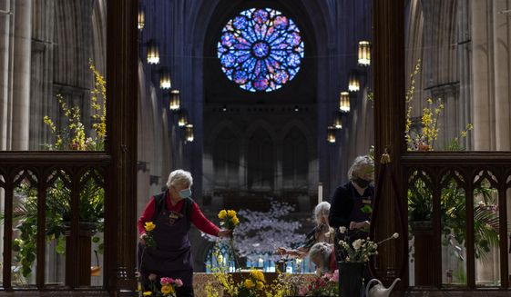 Washington National Cathedral Altar Guild members Anne Bowen, left, and Anne Roulhac, right, arrange flowers in preparation for the virtual Easter Sunday worship services at the Washington National Cathedral in Washington, Saturday, April 3, 2021. The Washington National Cathedral offers online worship services because to the COVID-19 pandemic. (AP Photo/Carolyn Kaster) ** FILE **