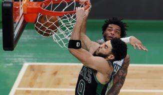 Boston Celtics' Jayson Tatum (0) dunks against Charlotte Hornets' Miles Bridges during the first half of an NBA basketball game, Sunday, April 4, 2021, in Boston. (AP Photo/Michael Dwyer)