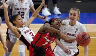 Arizona guard Aari McDonald (2) passes between Stanford guard Anna Wilson (3) and forward Cameron Brink, right, during the second half of the championship game in the women's Final Four NCAA college basketball tournament, Sunday, April 4, 2021, at the Alamodome in San Antonio. (AP Photo/Eric Gay)