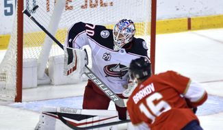 Florida Panthers center Aleksander Barkov (16) hits the post on a shot against Columbus Blue Jackets goaltender Joonas Korpisalo during the first period of an NHL hockey game Sunday, April 4, 2021, in Sunrise, Fla. (AP Photo/Jim Rassol)