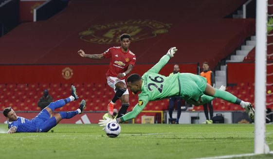 Manchester United's Marcus Rashford, centre, scores his side's opening goal during the English Premier League soccer match between Manchester United and Brighton and Hove Albion at Old Trafford, Manchester, England, Sunday, Apr. 4, 2021. (Phil Noble/Pool via AP)