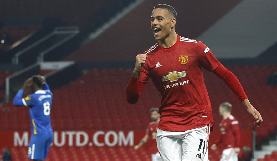 Manchester United's Mason Greenwood celebrates after scoring his side's second goal during the English Premier League soccer match between Manchester United and Brighton and Hove Albion at Old Trafford, Manchester, England, Sunday, Apr. 4, 2021. (Phil Noble/Pool via AP)