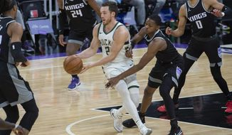 Milwaukee Bucks guard Pat Connaughton (24) is defended by Sacramento Kings guard De'Aaron Fox during the first quarter of an NBA basketball game in Sacramento, Calif., Saturday, April 3, 2021. (AP Photo/Randall Benton)