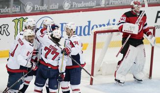 Washington Capitals' Alex Ovechkin (8) celebrates with teammates after scoring a goal as New Jersey Devils goaltender Mackenzie Blackwood (29) reacts during the second period of an NHL hockey game Sunday, April 4, 2021, in Newark, N.J. (AP Photo/Frank Franklin II)