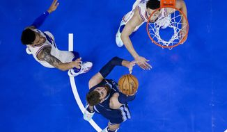 Memphis Grizzlies' Jonas Valanciunas, center, shoots the ball with Philadelphia 76ers' Ben Simmons, right, and Danny Green, left, defending during the first half of an NBA basketball game, Sunday, April 4, 2021, in Philadelphia. (AP Photo/Chris Szagola)