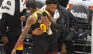 Utah Jazz's Donovan Mitchell, right, hugs Jordan Clarkson (00) after Clarkson came out of an NBA basketball game in the second half against the Orlando Magic, Saturday, April 3, 2021, in Salt Lake City. (AP Photo/Rick Bowmer)