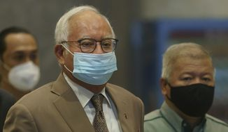 Former Malaysian Prime Minister Najib Razak, center, wearing a face mask arrives at Court of Appeal in Putrajaya, Malaysia, Monday, April 5, 2021. The court Monday began hearing an appeal by Najib  to overturn his conviction and 12-year jail sentence linked to the massive looting of the 1MDB state investment fund that brought down his government in 2018. (AP Photo/Vincent Thian)