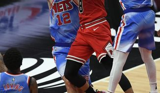 Chicago Bulls' Zach Lavine (8) shoots between Brooklyn Nets' Bruce Brown (1) and Joe Harris (12) during the second half of an NBA basketball game Sunday, April 4, 2021, in Chicago. Chicago won 115-107. (AP Photo/Paul Beaty)