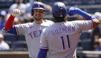 Texas Rangers Nate Lowe celebrates his three-run home run with teammate Ronald Guzman during the third inning of a baseball game at Kauffman Stadium in Kansas City, Mo., Sunday, April 4, 2021. (AP Photo/Orlin Wagner)