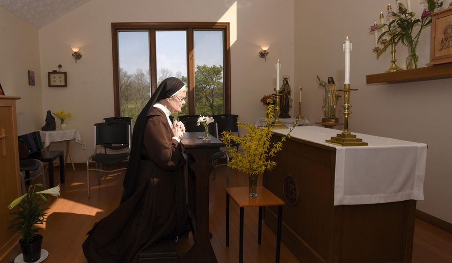 The Rev. Sister Barbara Smith, of the Order of Discalced Carmelites, prays on a prayer bench that belonged to The Rev. Mychal Judge, the Fire Department of New York's chaplain who died in the 2001 attacks on the World Trade Center, at the Episcopal Carmel of Saint Teresa in Rising Sun, Md., on Sunday, April 4, 2021. The Episcopal Carmel of Saint Teresa donated the prayer bench to the National Sept. 11 Memorial and Museum, representatives of which acquired the bench later in the morning. (AP Photo/Steve Ruark)