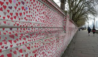 People jog past the 'The National COVID Memorial Wall' on the south bank of the Thames in front of St. Thomas' hospital and opposite the House of Parliament in London, Sunday April 4, 2021. Hearts are being drawn onto the wall in memory of the many thousands of people who have died in the UK from coronavirus, with organizers hoping to reach their target of 150,000 hearts by the middle of next week. (AP Photo/Tony Hicks)